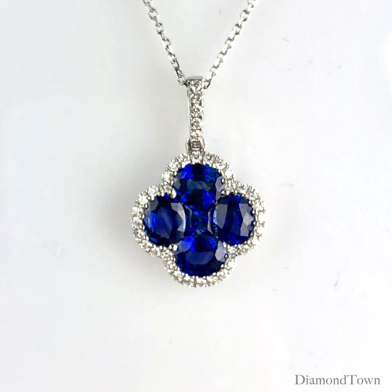 This beautiful pendant features a clover design made of four oval cut and one princess cut vivid blue sapphires (total weight 1.81 carats), surrounded by a halo of round diamonds (total weight 0.19 carats).  There is a seasonal promotion available