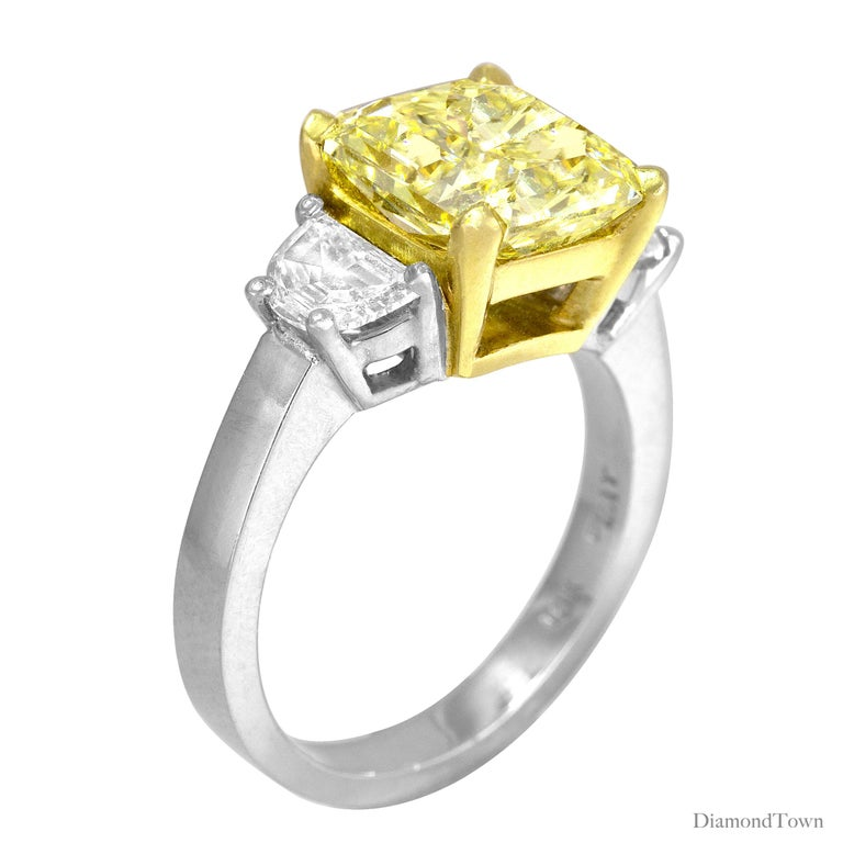 This gorgeous handcrafted ring features a 4.09 carat GIA certified radiant cut Natural Fancy Yellow diamond center, flanked by two half-moon diamonds, bringing the total diamond weight to 5.08 carats. The ring is set in Platinum and 18k White