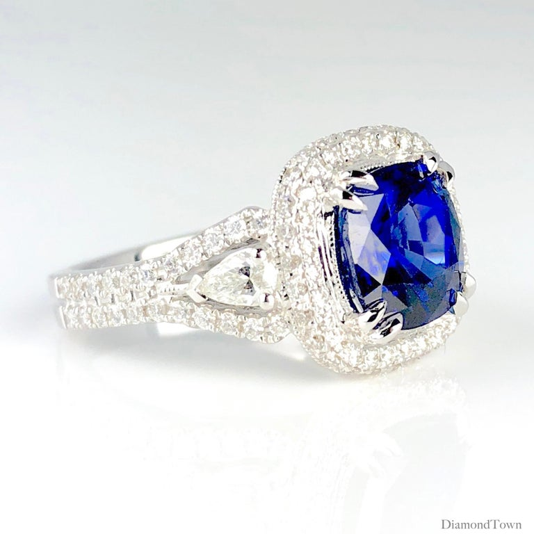 This ring sparkles with a 3.59 carat Cushion Cut Blue Sapphire center, surrounded by a halo of round white diamonds. The split shank starts with a pear shaped diamond, surrounded by round white diamonds, which also follow through the front and back