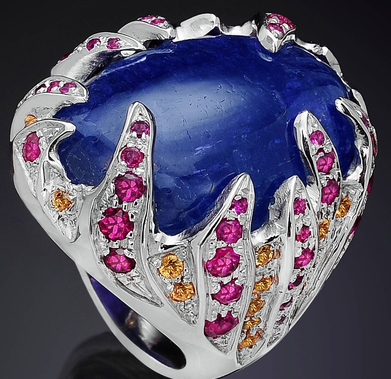 Wonderful cabochon tanzanite gemstone 38 ctw set in 18k white gold with rubies 2.46 ctw and yellow sapphires 0.77 ctw. US finger size 6.5, it can be resized before shipment. It is handcrafted in Italy by Botta Gioielli and it  is stamped with the