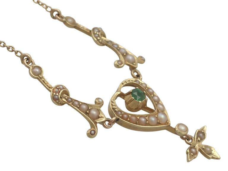 This fine and impressive peridot necklace has been crafted in 15k yellow gold.  The necklace displays a feature 0.12 ct round cut peridot bezel set to the centre of a pierced decorated, pearl set, heart shaped setting.  A leaf design trefoil shaped