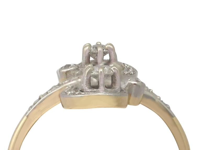 This fine and impressive antique diamond twist ring has been crafted in 18k yellow gold with an 18k white gold setting.  The pierced decorated claw settings display two Old European round cut diamonds claw set vertically on a twist.  The feature
