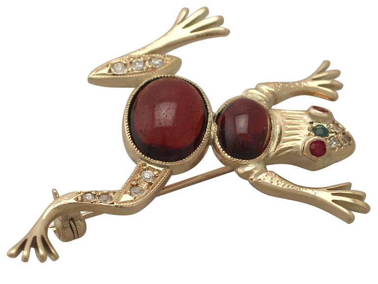 A fine and impressive 0.22 carat diamond. 5.95 carat garnet, 0.10 carat ruby and emerald, and 14 karat yellow gold 'frog' brooch; part of our diverse vintage jewellery collections  This fine and impressive vintage frog brooch has been crafted in 14k