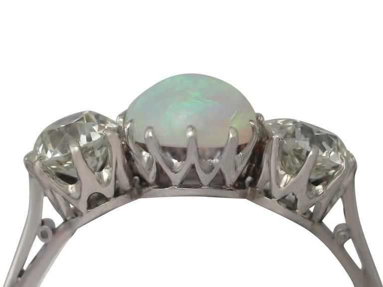 A stunning, fine and impressive antique 0.73 Carat opal and 1.08 Carat diamond, 18 karat white gold engagement ring; part of our diverse antique jewelry and estate jewelry collections  This stunning, fine and impressive antique opal and diamond