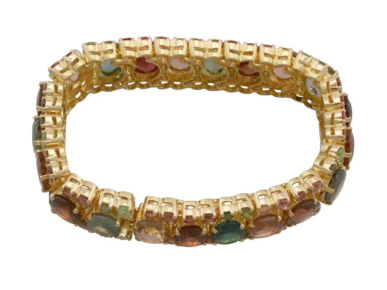 A stunning 96.65 carat tourmaline and peridot, 18 karat yellow gold bracelet; part of our diverse gemstone jewelry and estate jewelry collections  This stunning, fine and impressive tourmaline bracelet has been crafted in 18 k yellow gold.  The