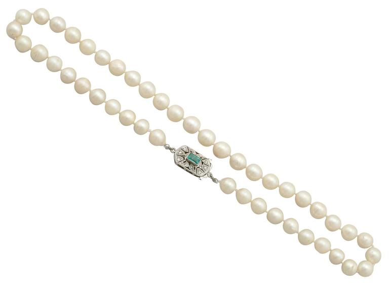 An impressive cultured pearl and 0.70 carat emerald, 0.10 carat diamond and 9 karat white gold single strand necklace; part of our diverse vintage jewelry collections  This fine and impressive single strand cultured pearl necklace consists of