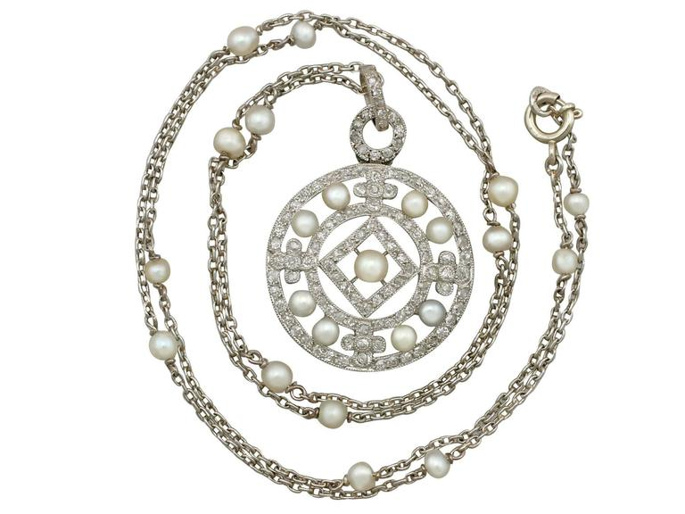 A stunning antique seed pearl, 1.11 carat diamond and platinum pendant on a vintage pearl and 14 karat white gold chain; part of our diverse antique jewelry collections.  This stunning, fine and impressive antique diamond and pearl pendant has been