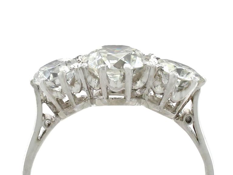 A stunning vintage 2.20 carat diamond and platinum three stone cocktail ring; part of our diverse vintage jewelry and estate jewelry collections  This stunning, fine and impressive trilogy ring has been crafted in platinum.  The pierced decorated,