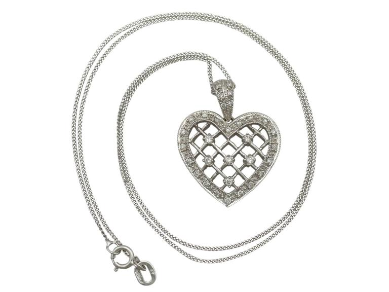 A fine and impressive vintage 0.28 carat diamond and 18 karat white gold heart shaped pendant; part of our diverse vintage jewelry and estate jewelry collections  This fine and impressive diamond heart pendant has been crafted in 18k white
