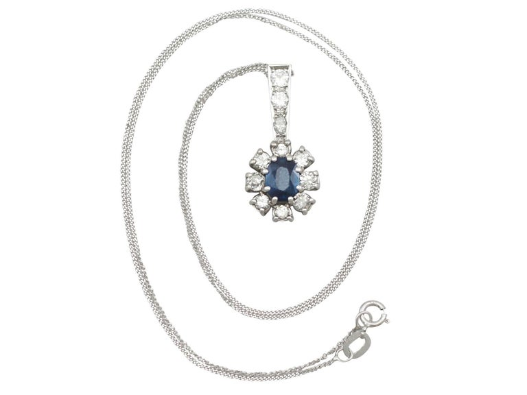 An impressive vintage 1.02 carat blue sapphire and 0.86 carat diamond, 18 karat white gold cluster pendant; part of our diverse vintage jewelry and estate jewelry collections  This fine and impressive sapphire cluster pendant has been crafted in 18k
