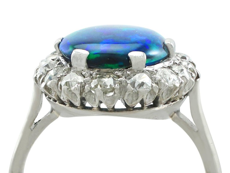 A stunning antique 1930's 1.89 carat black opal and 0.78 carat diamond, platinum cluster style dress ring; part of our diverse gemstone jewelry collections  This stunning, fine and impressive antique black opal ring has been crafted in