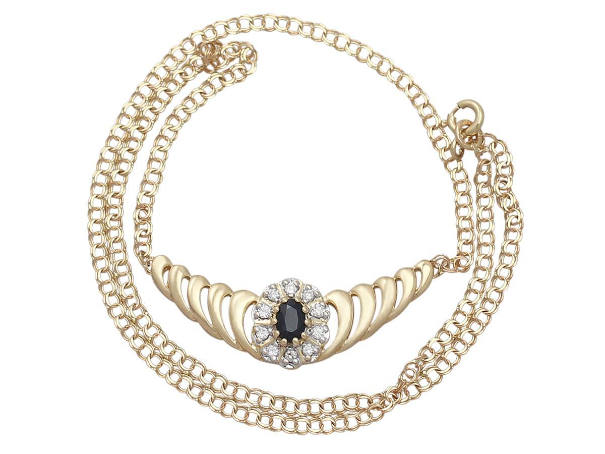 A very good and impressive 0.36 carat natural blue sapphire and 0.45 carat diamond, 18 karat yellow gold necklace; part of our contemporary and estate jewelry collections.  This contemporary sapphire and diamond necklace has been crafted in 18k