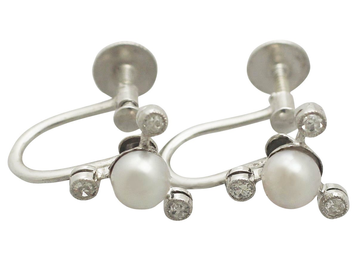 A fine and impressive pair of vintage 0.18 carat diamond and pearl, 9 karat white gold earrings; part of our vintage estate jewelry collections.  These impressive vintage pearl and diamond earrings have been crafted in 9 ct white gold.  Each setting