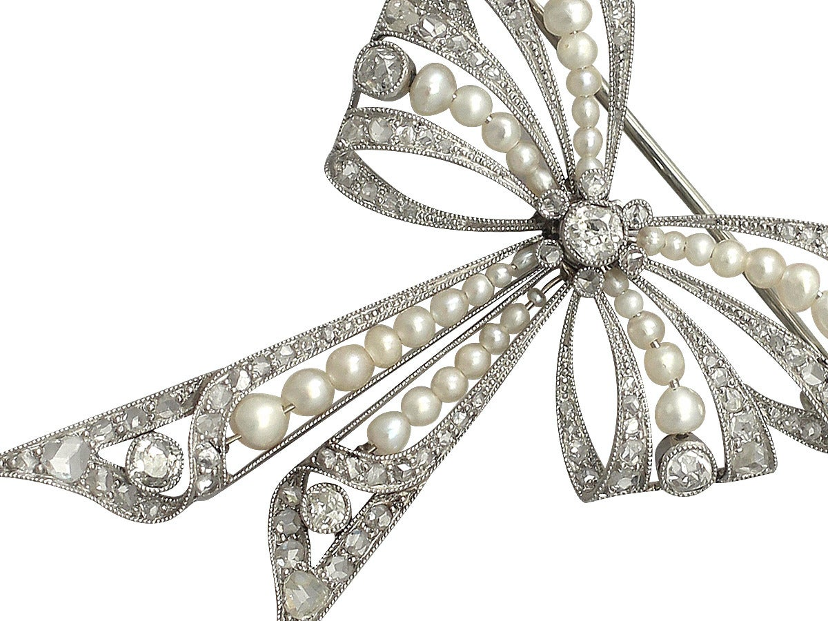 A fine and impressive platinum pearl bow brooch with 0.68 carat diamonds; part of our antique jewelry and estate jewelry collections  This stunning fine and impressive antique Victorian pearl bow brooch has been crafted in platinum.  The delicate