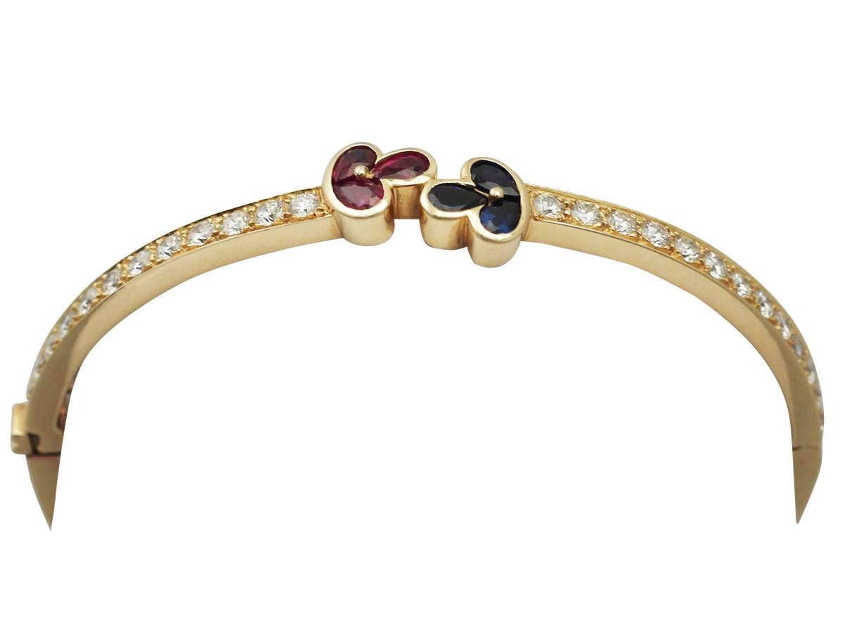 A fine and impressive vintage French 1.05 carat natural ruby, 0.98 carat natural blue sapphire and 2.16 carat diamond, 18 karat yellow gold bangle; part of our vintage jewelry/jewelry collection  This impressive vintage bangle has been crafted in 18