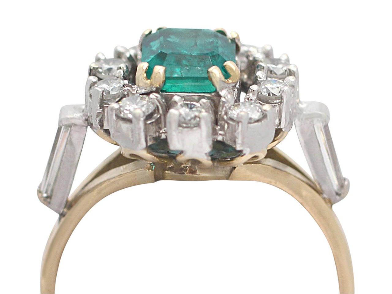 A fine and impressive vintage 0.84 carat natural emerald and 0.50 carat diamond, 18 karat yellow gold cluster ring; part of our vintage jewelry and estate jewelry collections  This impressive vintage cluster ring has been crafted in 18k yellow gold