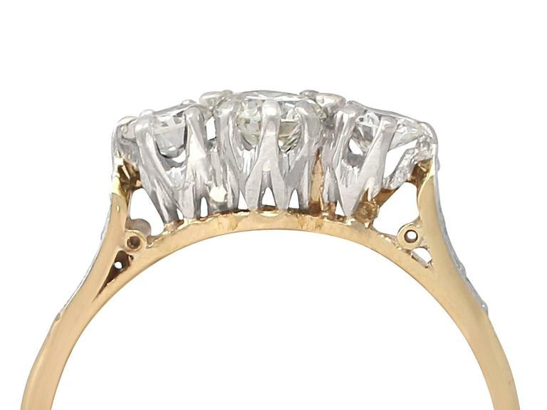 A fine and impressive antique 0.68 carat diamond and 18 karat yellow gold, platinum set three stone ring; part of our diverse diamond jewelry and estate jewelry collections  This fine and impressive diamond trilogy ring has been crafted in 18k