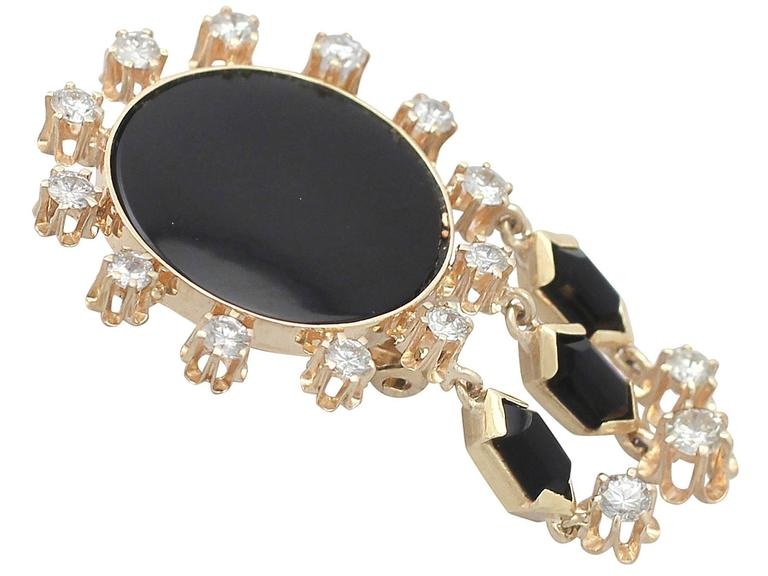 A stunning, fine and impressive pair of vintage black onyx and 1.40 carat diamond, 14 karat yellow gold Art Deco style drop earrings; part of our diverse vintage jewelry and estate jewelry collections  These stunning diamond and onyx earrings have