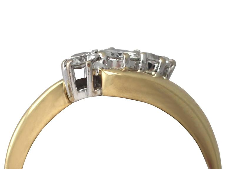 A fine and impressive contemporary 0.46 carat diamond and 18 karat yellow gold, 18 karat white gold set trilogy twist ring; part of our diamond jewelry and estate jewelry collections  This fine and impressive trilogy twist ring has been crafted in
