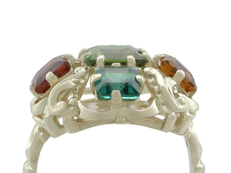 A 1.30 carat peridot, 0.74 carat citrine, 0.88 carat garnet, 0.62 carat amethyst, 0.66 carat tourmaline and 14 carat yellow gold cocktail ring; part of our diverse vintage jewellery collections.  This fine and impressive multi gemstone ring has been