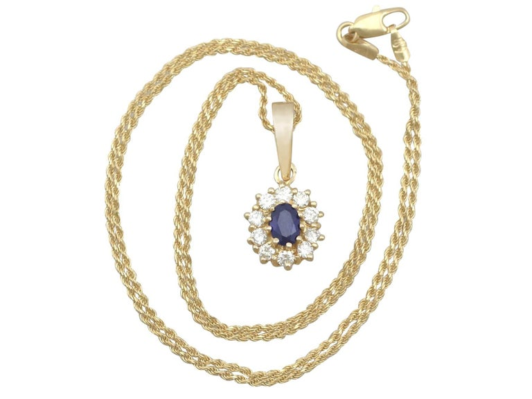 An impressive vintage 0.62 carat blue sapphire and 0.35 carat diamond, 18 carat yellow gold cluster pendant; part of our diverse gemstone jewellery collections.  This fine and impressive blue sapphire and diamond pendant has been crafted in 18k