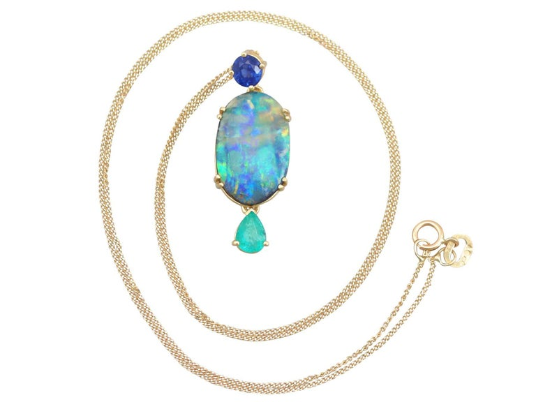 An impressive vintage 4.06 carat boulder opal, 0.40 carat emerald, 0.30 carat sapphire and 18 karat yellow gold pendant; part of our diverse gemstone jewellery collections  This fine and impressive vintage boulder opal pendant has been crafted in