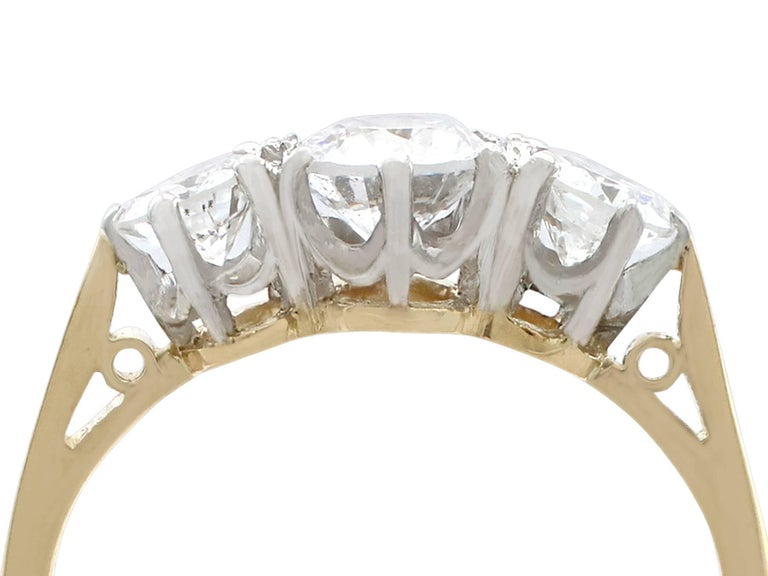 A fine and impressive vintage 1.27 carat diamond and 18 karat yellow gold, platinum set three stone/trilogy ring; part of our vintage jewelry and estate jewelry collections  This fine vintage three stone engagement ring has been crafted in 18k