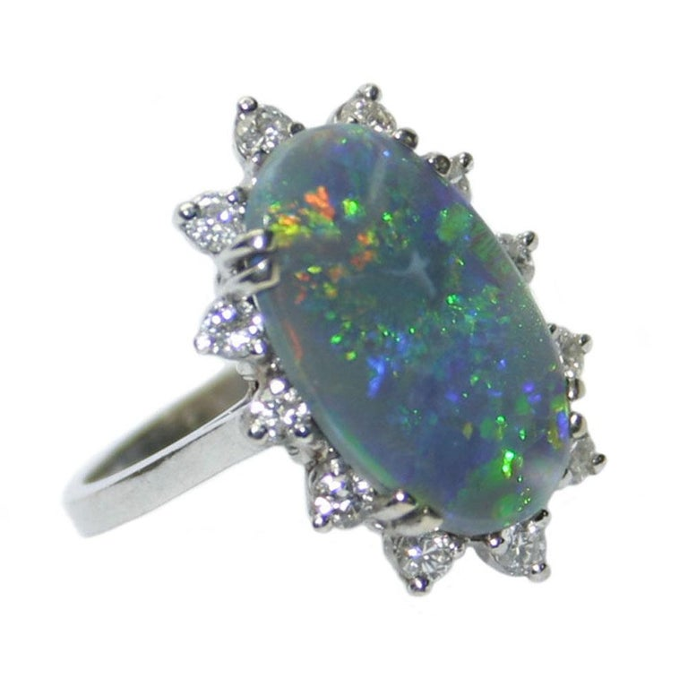 This Is A 14k White Gold Ladies Australian Black Opal And Diamond Ring. The Main Stone Is A Solid 17 X 10 Millimeter Oval Opal. The Opal Is Accented By 12 Round Cut Diamonds With A Total Weight Of 0.24 Carats. With SI Clarity And H Color. The Ring