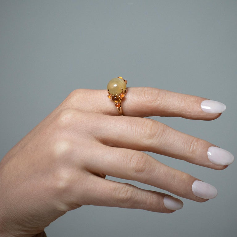 A luxurious cocktail ring features a round 12mm cabochon-cut lemon moonstone center stone, with side details of carnelian and citrine. Set in 18k yellow gold, size 7.5. Ring can be resized to fit your finger.  Daria de Koning's one-of-a-kind