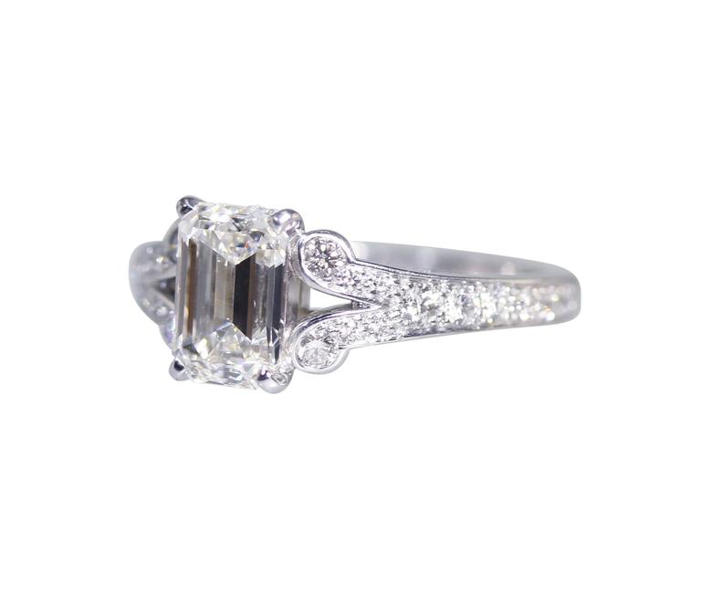 A platinum and diamond ring by Cartier, set in the center with an emerald-cut diamond weighing 1.55 carats, flanked by 24 round diamonds weighing approximately 0.50 carat, gross weight 5.3 grams, measuring 1/4 by 3/4 by 7/8 inch, size 4 with sizing