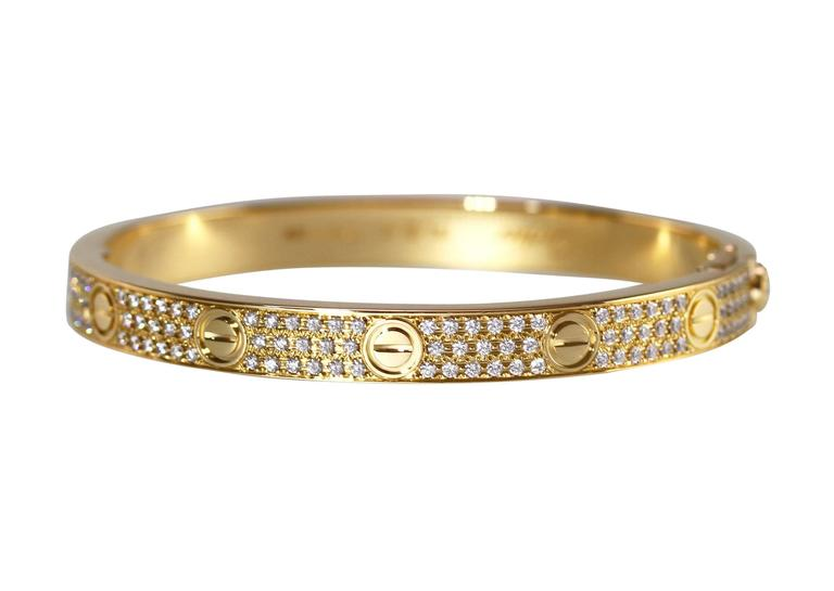An 18 karat yellow gold and diamond 'Love' bangle bracelet by Cartier, the bangle applied with numerous screw motifs and pave-set with 204 diamonds weighing 2.00 carats, length 6 1/4 inches, width 1/4 inch, gross weight 47.2 grams, size 17, signed