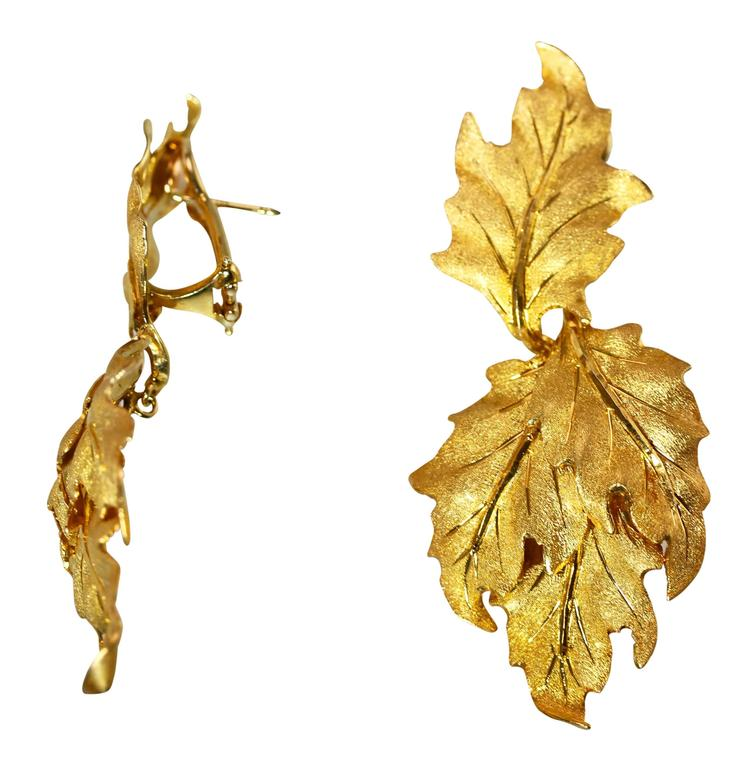 A pair of 18 karat yellow gold earclips by Buccellati, Italy, designed as textured gold leaf tops each supporting pendants of three textured gold leaves, measuring 2 1/2 by 1 inches, gross weight 27.4 grams, signed M. Buccellati, Italy, with Italian