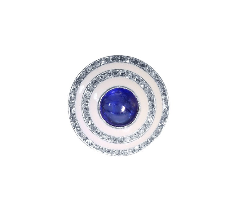 Edwardian Platinum, Sapphire, Diamond and White Enamel Ring • Center bezel-set with a round cabochon sapphire approximately 4.00 carats • 80 rose cut diamonds weighing approximately 1.20 carats • Size 8 1/2, gross weight of 9.7 grams,
