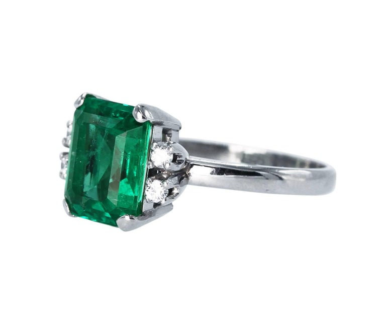 Platinum, Emerald and Diamond Ring • Emerald-cut emerald weighing 2.76 carats • AGL report stating the emerald to be of Colombian origin with Traditional, Insignificant oil • 4 round diamonds approximately 0.12 carat • Size 6 1/4, gross