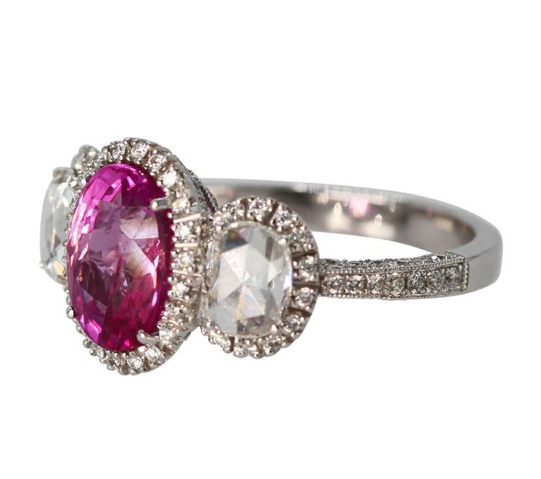 18 Karat White Gold, Pink Sapphire and Diamond Ring • Oval pink sapphire weighing approximately 2.50 carats •2 rose-cut diamonds weighing approximately 0.70 carat • 180 round diamonds weighing approximately 1.80 carats • Gross weight 6.7