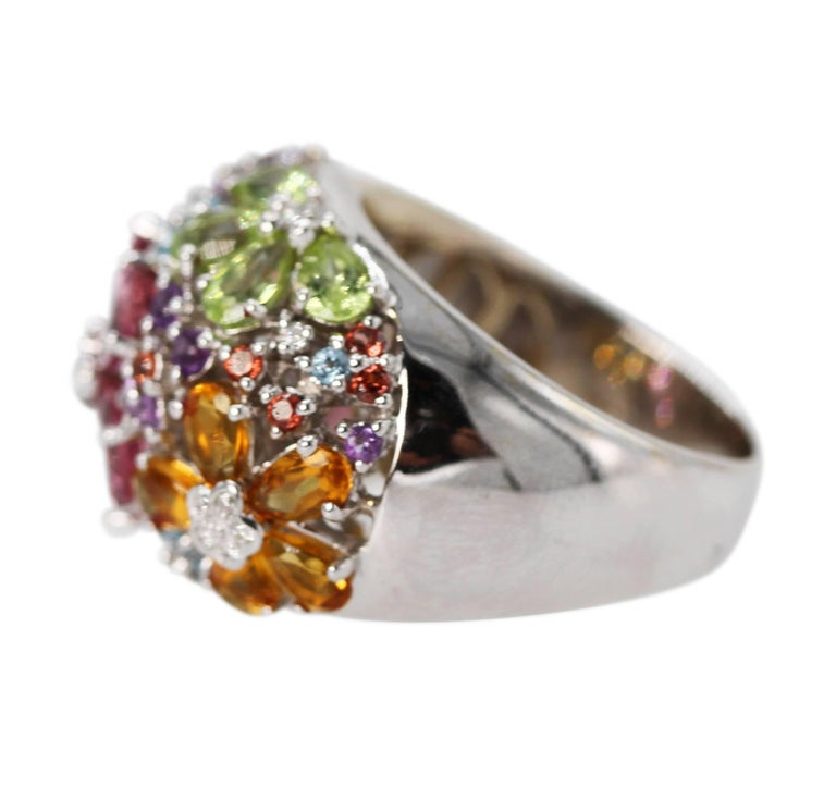 18 Karat White Gold, Multi-Colored Gem and Diamond Ring • Marked 18k 750 with makers mark • 5 pear shape-shaped citrines, 5 blue topaz, 5 pink tourmalines, and 4 pear-shaped peridots • 14 round amethysts, 10 round citrines, 9 round blue