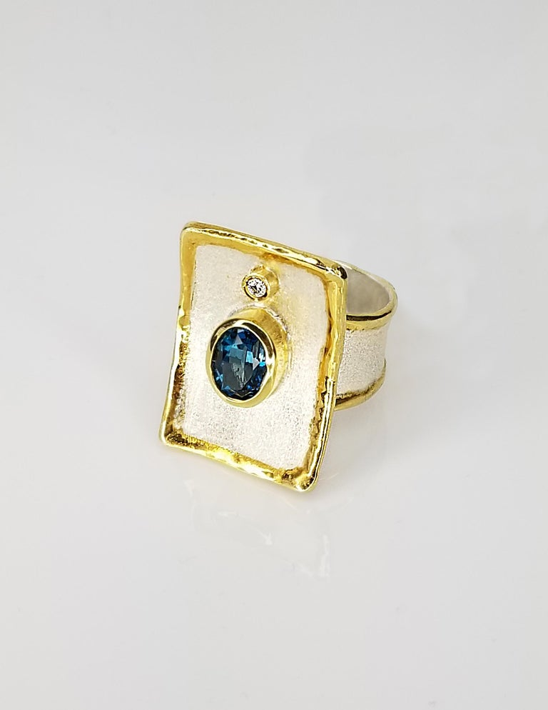 Yianni Creations Midas Collection 100% Handmade Artisan Ring from Fine Silver with an overlay of 24 Karat Yellow Gold features a 1.25 Carat London Blue Topaz accompanied by 0.03 Carat Diamond complimented by unique techniques of craftsmanship -