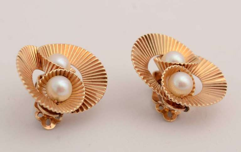 Classic Retro earrings of 14 karat gold and pearls. Fluted swirls meet to cradle two pearls. Measurements are 15/16