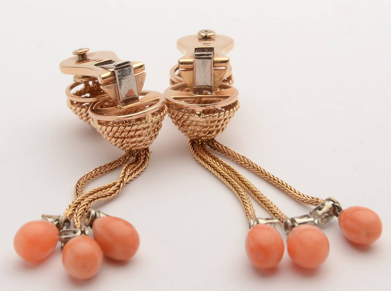 Unusual coral and diamond earring with a variety of textures and dimensions. The two domes are twisted gold with foxtail over the top to  give the appearance of being a continuation of the three foxtail dangles. The pear shaped coral stones are