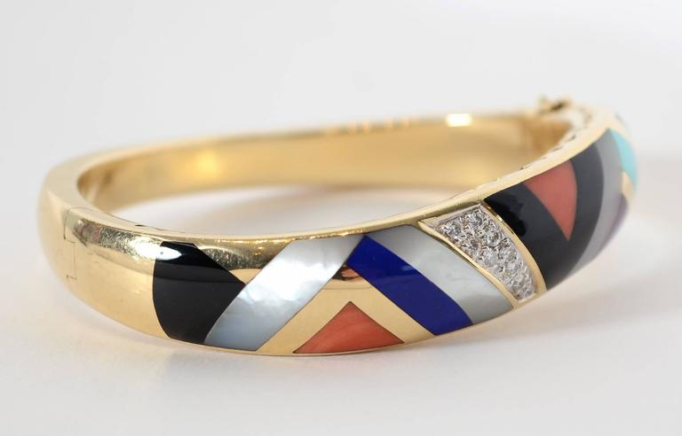 Chevron pattern bracelet by Asch Grossbardt in which the entire bracelet is an undulating form. The inlaid multicolored stones include black onyx; mother of pearl; coral; turquoise; malachite and diamonds. The gold sides of the bracelet have cutout