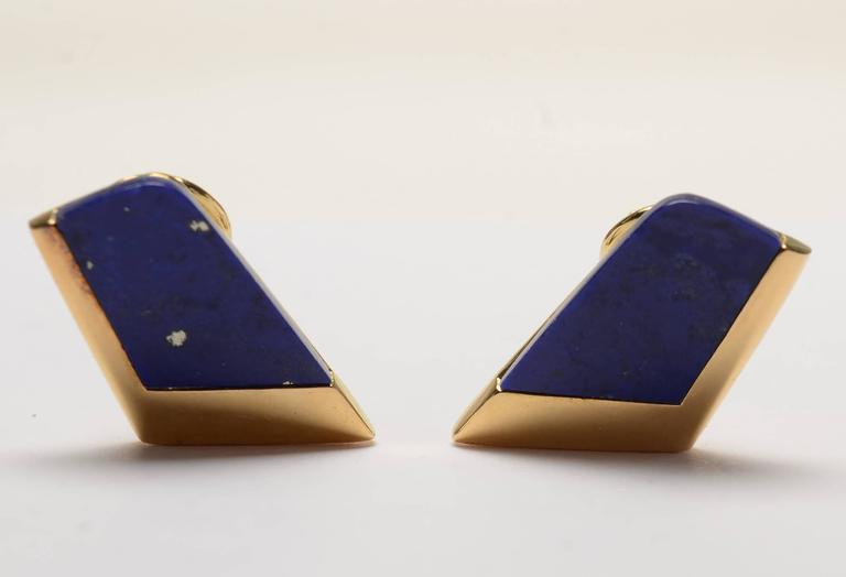 "Trim and  tailored trapezoidal shaped earrings of lapis lazuli set in 18 karat gold. They have a maker's mark of the letter L within a triangle, a mark with which I am not familiar. Measurements are 7/8 long x 1/2"" at the widest. Clip and post backs"
