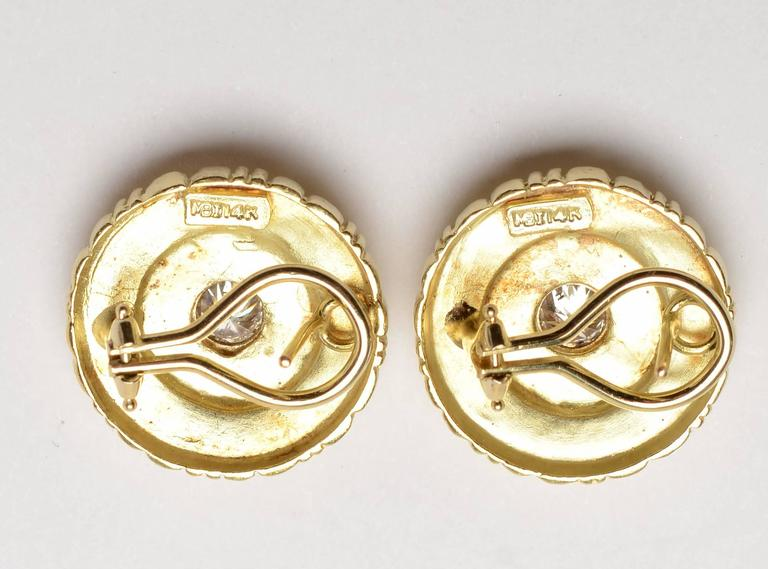 These round gold earrings have a stepped design of rectangles, bars and balls. They radiate from the half carat center diamond.  Backs are posts and clips. A maker's mark is not quite decipherable. Measurement is 13/16