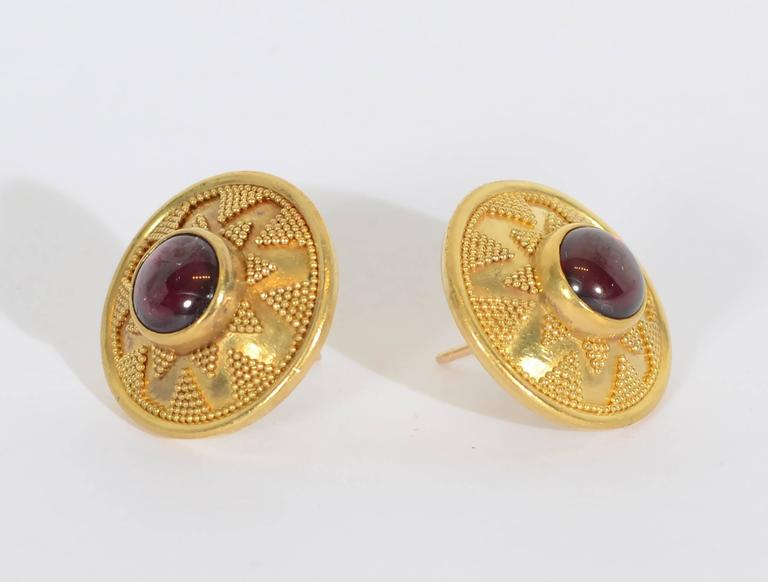 These ear studs demonstrate the finest of Etruscan gold work. Central cabochon garnets are the center of a star like design comprised of tiny, tiny balls. The earrings are 3/4