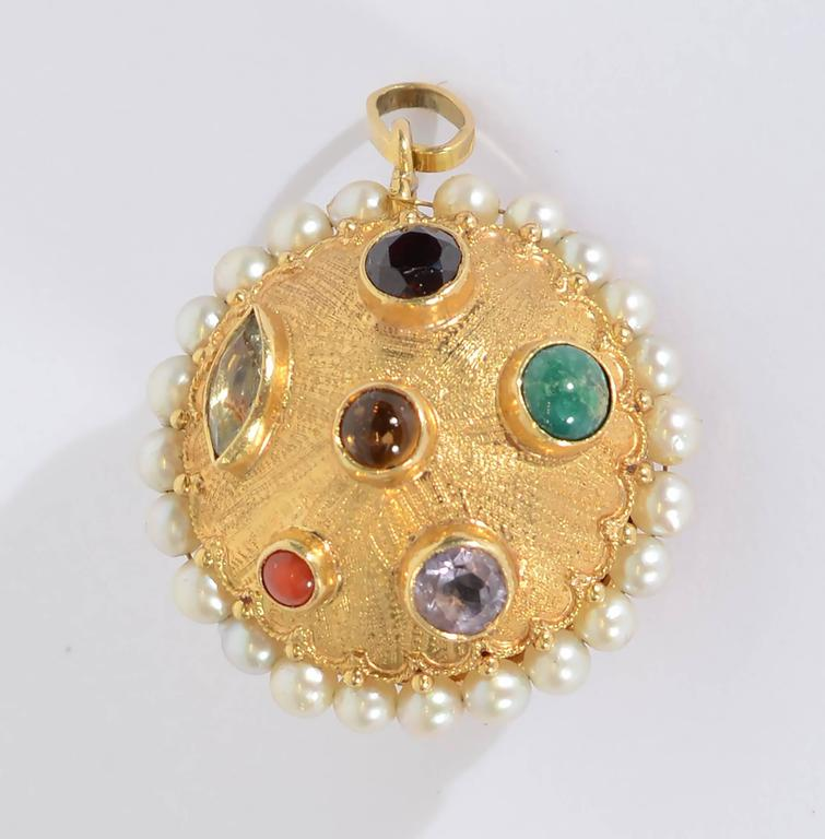 Beautifully made reversible 18 karat  gold domed disc with a variety of semiprecious stones. They include: amethyst; citrine; garnet; coral and turquoise. Stones are both faceted and cabochon. The entire disc is surrounded with a gold swag and a