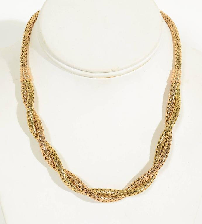 Unusual Retro necklace of pink and yellow gold in a herringbone pattern. The central panel intertwines both colors while the banding and part behind the neck are pink. The difference in the two colors is subtle but evident. The necklace measures 16
