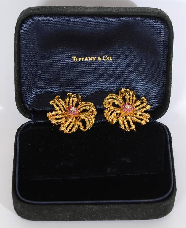 Tiffany 18 karat earrings with six swirling arms. Each arm is made of three loops  - the center is twisted gold and smooth with bands on either side. The center of each earring is a diamond surrounded by five rubies.also giving the effect of a star.