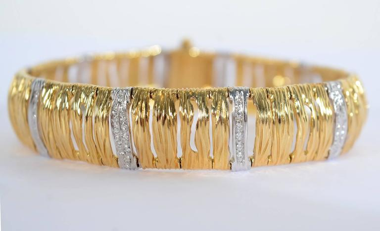 Roberto Coin 18 karat gold bracelet with the interesting texture he refers to as elephant skin. The links are interspersed with alternate single and double rows of diamonds. The bracelet is 9/16