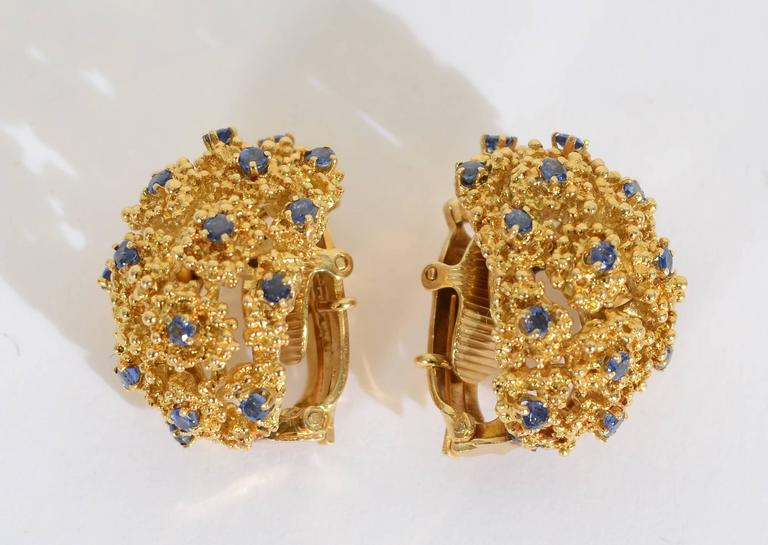 "Tiffany half round  earrings with sapphires surrounded by clusters of heavily textured irregular circles. The earrings are 18 karat gold. Clip backs can be converted to posts. They are 1 inch long and 3/4 "" wide."