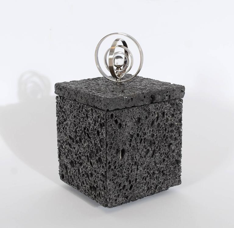 This box made of volcanic lava is topped with a sterling silver and crystal ball finial. The four silver circles are movable to create either a flat or three dimensional form. The interior of the box is lined with red leather. The box measures 3 1/8