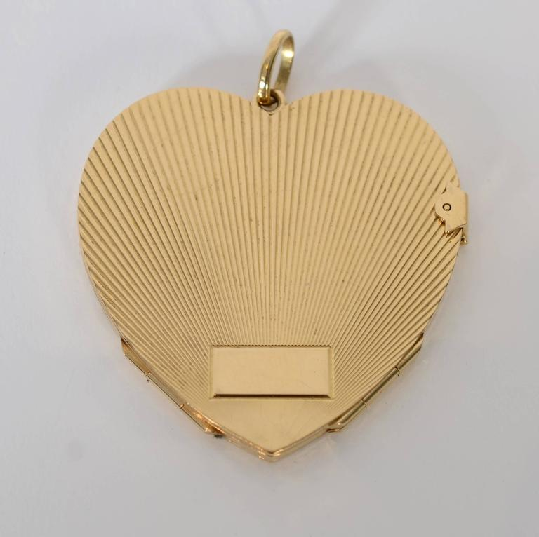This 18 karat gold Retro heart locket is unusual in two ways. It is larger than most at 2 inches in length and width and it opens to four compartments rather than the usual two. The back has a rectangular plaque that can be engraved. Textured lines
